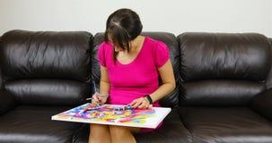 Een jonge vrouwenverven op canvas stock footage