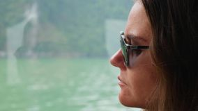 Een jonge vrouwenzitting binnen een boot in een witte sweater en zonnebril bekijkt de mooie mening van de baai stock footage