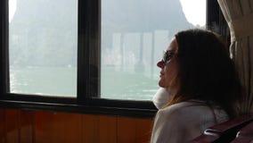 Een jonge vrouwenzitting binnen een boot in een witte sweater en zonnebril bekijkt de mooie mening van de baai stock videobeelden