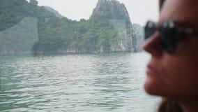 Een jonge vrouwenzitting binnen een boot in een witte sweater en zonnebril bekijkt de mooie mening van de baai stock video