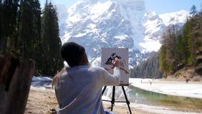Een jonge vrouwenzitting op de stoel in Dolomiet Het trekken op een canvas stock video