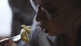 Een jonge vrouwenzitting in een restaurant die hete lasagna's eten stock footage