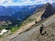 Een jonge wandelaar die Rocky Mountains op een backcountry stijging langs de spectaculaire Northover-Randsleep onderzoeken in Kan stock foto