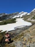 Een jonge wandelaar die wat zoet water van snowmelt verzamelen van royalty-vrije stock fotografie