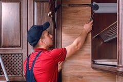 Een jonge werknemer assembleert modern houten keukenmeubilair royalty-vrije stock fotografie