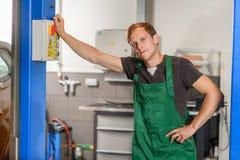 Een jonge werktuigkundige in een slinger, die op een blauwe autolift leunen stock foto