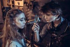 Een jonge wetenschapper bekijkt een meisje in een vergrootglas stock afbeeldingen