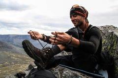 Een jonge witte Kaukasische mens met een lichte unshavenness treft voor een nieuwe dag van wandeling in de bergen en de bindende  stock foto