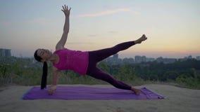 Een jonge yoga van vrouwenpraktijken op een berg op de achtergrond van een grote stad stock videobeelden