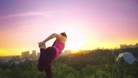 Een jonge yoga van vrouwenpraktijken op een berg op de achtergrond van een grote stad Gezonde vrouw die sporten doen bij zonsonde stock videobeelden