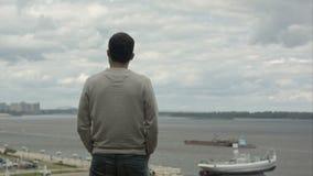 Een jonge zakenman bevindt zich door de rivier, kijkt vooruit en denkt stock video