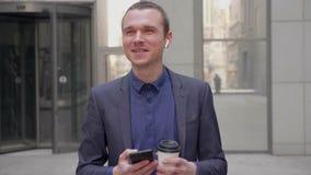 Een jonge zakenman bevindt zich op de straat en glimlacht met draadloze oortelefoons in zijn oren stock footage