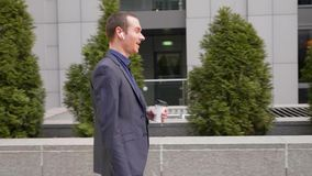 Een jonge zakenman die met draadloze hoofdtelefoons lopen en communiceert gelukkig op een telefoongesprek stock videobeelden