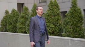 Een jonge zakenman die met draadloze oortelefoons en besprekingen over het telefoongesprek lopen stock footage