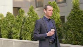 Een jonge zakenman die met draadloze oortelefoons en besprekingen over het telefoongesprek lopen stock videobeelden
