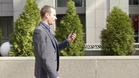 Een jonge zakenman die onderaan de straat en de besprekingen over het videogesprek lopen stock footage