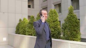 Een jonge zakenman die onderaan de straat lopen en communiceert gelukkig op het telefoongesprek stock footage