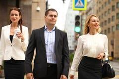 Een jonge zakenman die op de straat met hun secretaresses lopen Stock Afbeelding