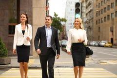 Een jonge zakenman die op de straat met hun secretaresses lopen Royalty-vrije Stock Foto