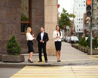 Een jonge zakenman die op de straat met hun secretaresses lopen Stock Fotografie