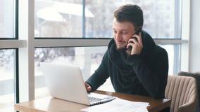 Een jonge zakenman die op de telefoon spreken en bij laptop in een koffie werken stock footage