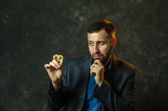 Een jonge zakenman houdt een muntstuk van bitcoite in zijn hand royalty-vrije stock fotografie