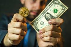 Een jonge zakenman houdt een muntstuk van bitcoite in zijn hand royalty-vrije stock foto