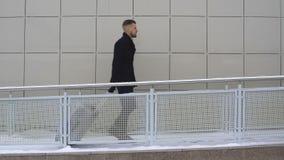 Een jonge zakenman loopt in een hotel met een koffer stock footage