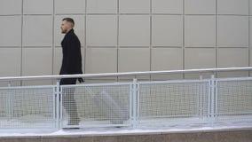 Een jonge zakenman loopt in een hotel met een koffer stock videobeelden