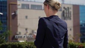 Een jonge zakenman met blond haar loopt onderaan de straat Het meisjes` s haar wordt, verwijderd op de achtergrond - bureau stock video
