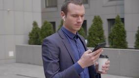 Een jonge zakenman met draadloze oortelefoons in zijn oren schrijft een bericht op smartphone stock footage