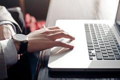 Een jonge zakenman raakt touchpad van laptop Royalty-vrije Stock Foto