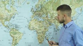 Een jonge zakenman stijgt zijn glazen op en onderzoekt een geografische kaart stock footage