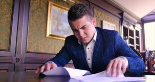 Een jonge zakenman zit in een elegant bureau en is ontevreden met een document contract, weigert te ondertekenen, boos, ongunstig stock footage