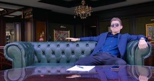 Een jonge zakenmanzakenman in een blauw kostuum en glazen zit als leervoorzitter in een luxeflat en wacht stock footage