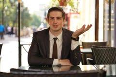 Een jonge zakenmanzitting in een koffie bij een lijst en het spreken stock foto