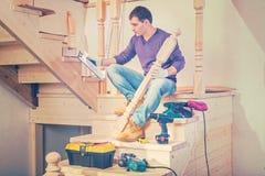 Een jonge zitting van de bouwcontractant op stappen van houten ladde Royalty-vrije Stock Foto