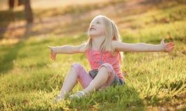 Een jonge zitting van het blondemeisje op het gras in het achterlicht in su stock fotografie