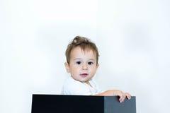 Een jonge zuigelingsjongen die uit een doos op een witte achtergrond gluren Stock Afbeeldingen