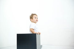 Een jonge zuigelingsjongen die uit een doos op een witte achtergrond gluren Stock Fotografie