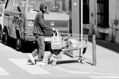 Een jonge zwarte mens die een boodschappenwagentje slepen Stock Afbeeldingen