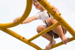 Een jongen beklimt de hoge gele ladder bij speelplaats op een sunn Stock Afbeeldingen