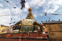 Een jongen beklimt een tempel in Katmandu, Nepal Stock Foto