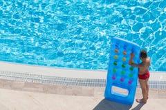 Een jongen bevindt zich op de rand van de pool royalty-vrije stock afbeeldingen