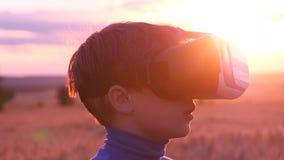 Een jongen bevindt zich op een tarwegebied bij zonsondergang in virtuele glazen stock video