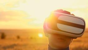 Een jongen bevindt zich op een tarwegebied bij zonsondergang in virtuele glazen stock footage