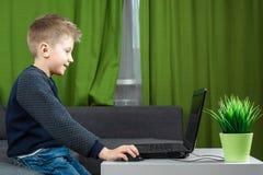 Een jongen bij laptop speelt spelen, of let op een video Het concept verslaving aan computerspelen, vage visie, geestelijk distri stock afbeeldingen