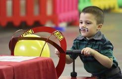 Een Jongen blaast een Ballon bij t-Rex Planeet, het Centrum van Tucson Expo op Royalty-vrije Stock Afbeeldingen