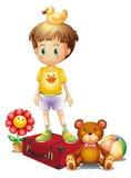 Een jongen boven de rode doos met zijn verschillend speelgoed Royalty-vrije Stock Afbeeldingen