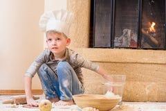 Een jongen in chef-kok` s hoeden dichtbij de open haardzitting op de keukenvloer met bloem wordt bevuild, spelend met voedsel, di stock foto